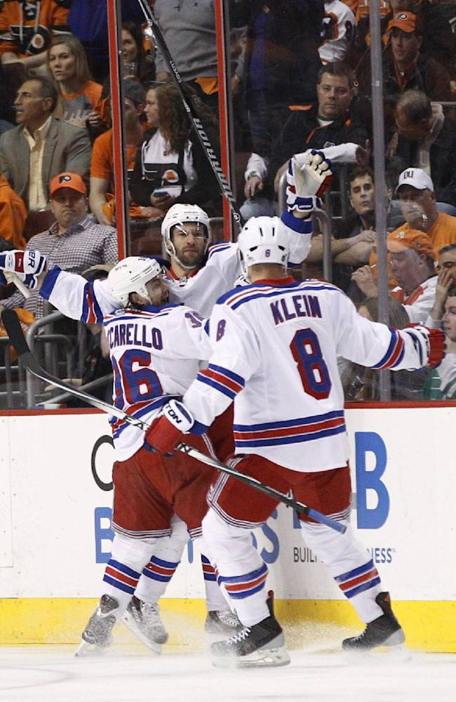 New York Rangers' Dominic Moore, center, celebrates his goal with Mats Zuccarello, left, and Kevin Klein during the first period in Game 4 of an NHL hockey first-round playoff series against the Philadelphia Flyers, Friday, April 25, 2014, in Philadelphia