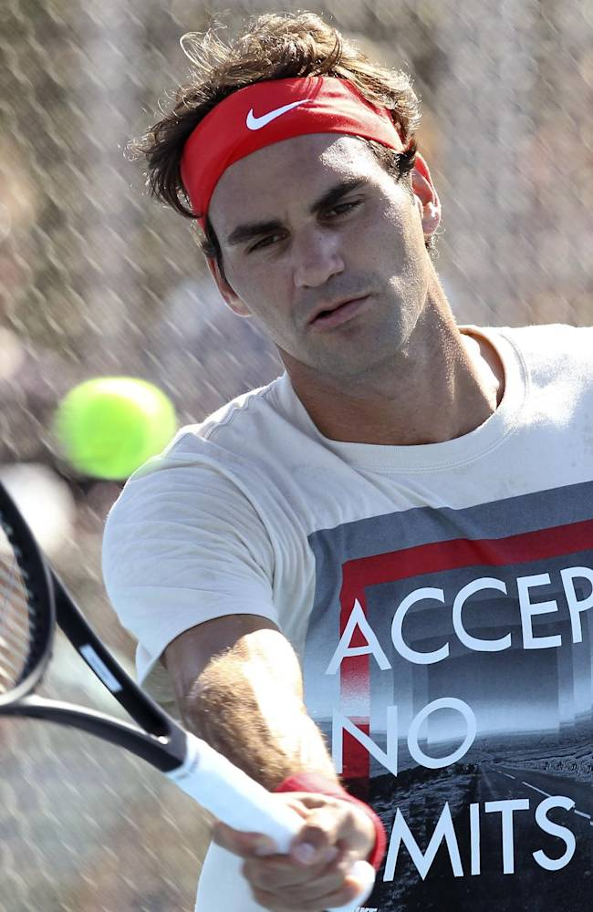 Roger Federer of Switzerland plays a shot during a training session at the Brisbane International tennis tournament in Brisbane, Australia, Sunday, Dec. 29, 2013