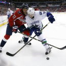 Washington Capitals center Brooks Laich (21) and Vancouver Canucks defenseman Chris Tanev (8) battle for the puck in the first period of an NHL hockey game, Tuesday, Dec. 2, 2014, in Washington The Associated Press