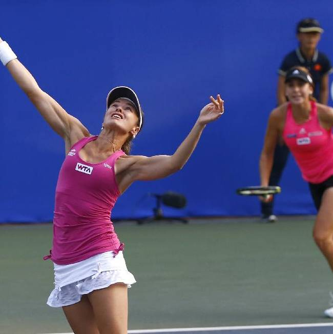 Martina Hingis, left, and Belinda Bencic, both of Switzerland, play Rika Fujiwara of Japan and Hsieh Shu-Ying Hsieh at their doubles first round match at the Japan Pan Pacific Open tennis tournament in Tokyo,Tuesday, Sept. 16, 2014