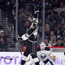 Los Angeles Kings left wing Tanner Pearson, top, jumps to stop a puck as Buffalo Sabres goalie Jhonas Enroth, of Sweden, looks on during the first period of an NHL hockey game, Thursday, Oct. 23, 2014, in Los Angeles. (AP Photo/Mark J. Terrill)