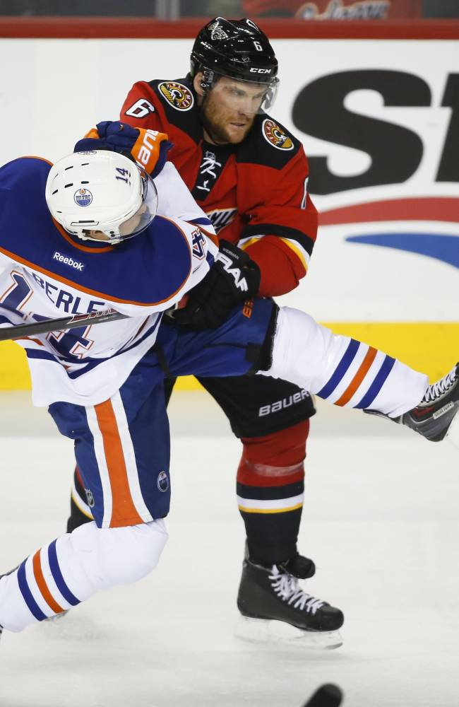 Edmonton Oilers' Jordan Eberle, left, gets knocked to the ice by Calgary Flames' Dennis Wideman during second period NHL hockey action in Calgary, Alberta