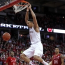 Wisconsin's Ryan Evans, center, dunks between Nebraska's Jordan Tyrance (11) and Dylan Talley during the second half of an NCAA college basketball game Tuesday, Feb. 26, 2013, in Madison, Wis. Wisconsin defeated Nebraska 77-46. (AP Photo/Andy Manis)