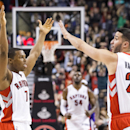 Toronto Raptors' Kyle Lowry, left, and Greivis Vasquez celebrate after Patrick Patterson center back, scores against Sacramento Kings during second half NBA basketball action in Toronto on Friday, March 7, 2014 The Associated Press