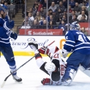 Toronto Maple Leafs defenseman Cody Franson (4) trips up New Jersey Devils forward Michael Ryder (17) in front of Maple Leafs goalie Jonathan Bernier (45) during the first period of an NHL hockey game, Thursday, Dec. 4, 2014 in Toronto The Associated Pres