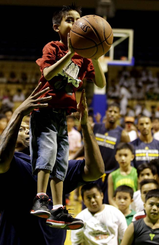 Former NBA basketball player Jalen Rose lifts to help a boy shoots the basketball during their meeting with Filipino fans Tuesday Oct. 8, 2013 at the Cuneta Astrodome at suburban Pasay city, south of Manila, Philippines. The Indiana Pacers will play against the Houston Rockets on Thursday in the first NBA game in this basketball-crazy Southeast Asian nation. The pre-season game is part of the NBA's global schedule that will have eight teams play in six countries this month