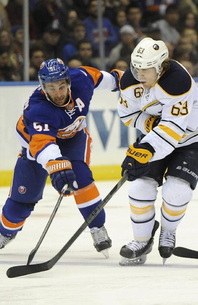 New York Islanders' Frans Nielsen (51) and Buffalo Sabres' Tyler Ennis (63) battle for the puck in the third period of an NHL hockey game on Saturday, March 15, 2014, in Uniondale, N.Y. Both Nielsen and Ennis scored during the Islanders 4-1 win
