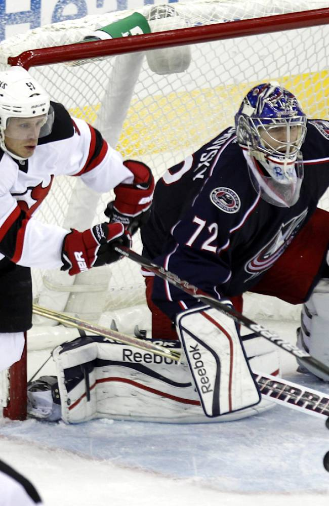 Columbus Blue Jackets goalie Sergi Bobrovsky, right, of Russia makes a stop in front of New Jersey Devils' Mattias Tedenby of Sweden, during the third period of an NHL hockey game in Columbus, Ohio, Tuesday, Oct. 22, 2013. Bobrovsky stopped 24 shots in the Blue Jackets 4-1 win