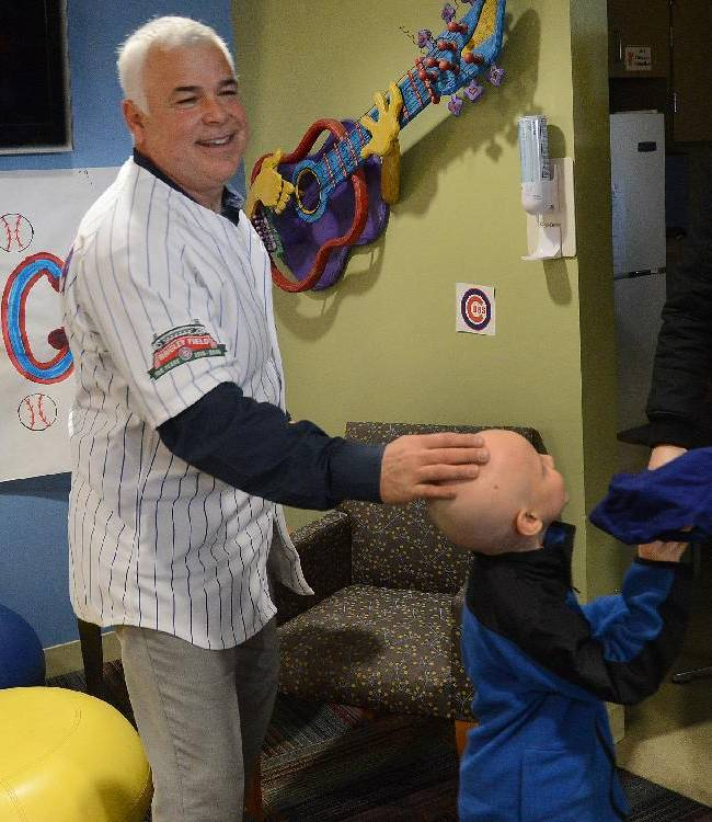 Chicago Cubs manager Rick Renteria autographs a hat for Gavin Fernstrom of East Dundee, Ill., as the Cubs new skipper visited with children at Advocate Children's Hospital in Park Ridge, Ill.,  Friday, Jan. 17, 2014