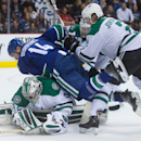 Dallas Stars' Jyrki Jokipakka, right, of Finland, checks Vancouver Canucks' Alex Burrows (14) as Stars' goalie Kari Lehtonen, of Finland, covers up the puck during the first period of an NHL hockey game in Vancouver, British Columbia, on Wednesday, Dec. 1
