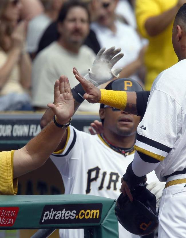 Pittsburgh Pirates' Jose Tabata (31) is greeted by manager Clint Hurdle, left, and Marlon Byrd, center, after scoring from third on a wild pitch by Chicago Cubs starting pitcher Travis Wood in the first inning of the baseball game on Sunday, Sept. 15, 2013, in Pittsburgh