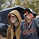 San Francisco Giants baseball fans Megan McPhillips, right, and Travis Saracco from Santa Rosa, Calif., wait in the rain for the start of the victory parade for the 2014 World Series Champion San Francisco Giants on Friday, Oct. 31, 2014 in San Francisco. (AP Photo/Jeff Chiu)