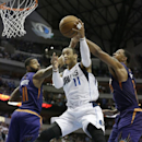Dallas Mavericks guard Monta Ellis (11) drives to the basket between Phoenix Suns forwards Markieff Morris (11) and Channing Frye (8) during the second half of an NBA basketball game on Saturday, April 12, 2014, in Dallas. The Mavericks won 101-98. (AP Photo/LM Otero)
