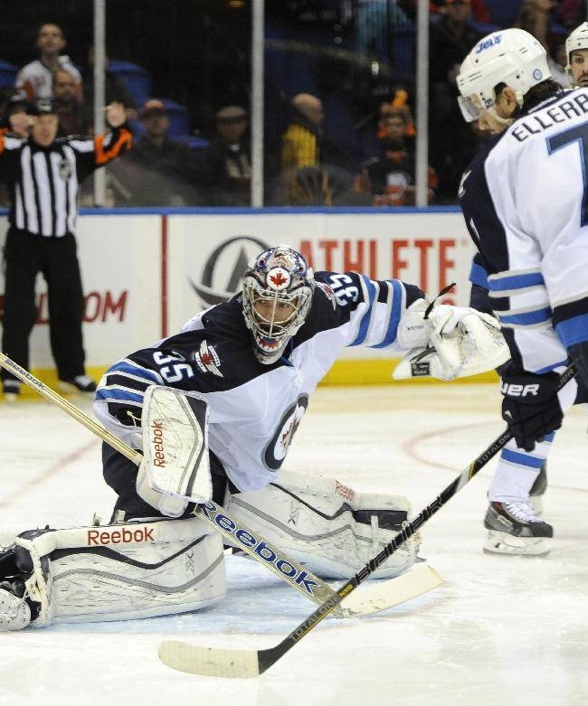 Winnipeg Jets goalie Al Montoya (35) kicks the puck away from the goal as Keaton Ellerby (7) defends against the New York Islanders in the second period of an NHL hockey game on Wednesday, Nov. 27, 2013, in Uniondale, N.Y. The Jets won 3-2