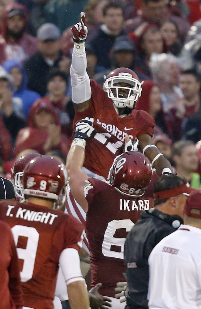 Oklahoma wide receiver Lacoltan Bester (11) celebrates a touchdown against Texas Tech with teammate Gabe Ikard (64) in the third quarter of an NCAA college football game in Norman, Okla., Saturday, Oct. 26, 2013. Oklahoma won 38-30