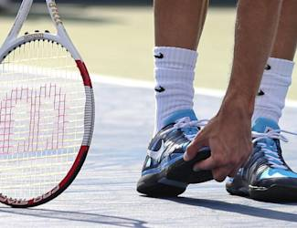 Grigor Dimitrov, of Bulgaria, checks the sole of his shoe between games against Gael Monfils, of France, during the fourth round of the 2014 U.S. Open tennis tournament, Tuesday, Sept. 2, 2014, in New York. (AP Photo/Mike Groll)