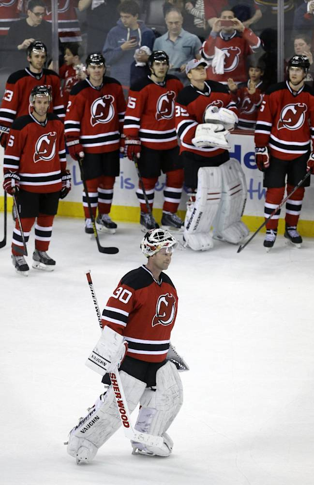 New Jersey Devils teammates watch as goalie Martin Brodeur skates for the crowd after an NHL hockey game against the Boston Bruins in Newark, N.J., Sunday, April 13, 2014. The Devils won 3-2