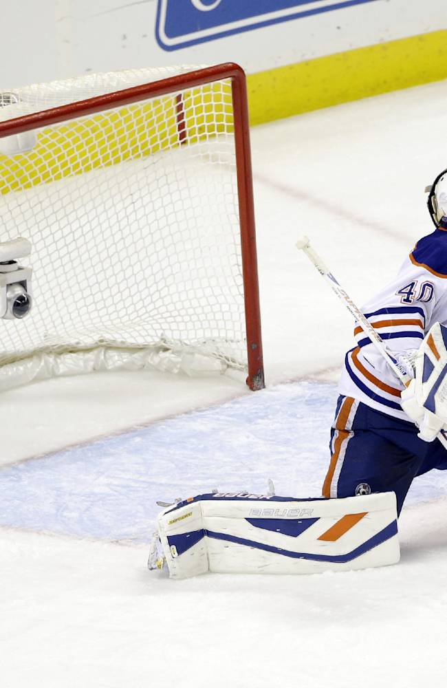 Edmonton Oilers goalie Devan Dubnyk is beaten for a goal  on a shot from San Jose Sharks' Logan Couture during the second period of an NHL hockey game on Thursday, Jan. 2, 2014, in San Jose, Calif