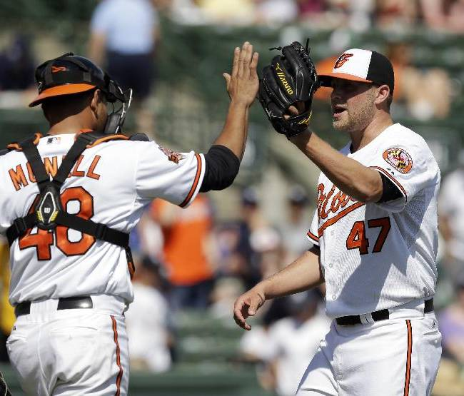 Baltimore Orioles catcher Johnny Monell (48) and relief pitcher Evan Meek (47) celebrate their 2-1 victory over the New York Yankees during a spring exhibition baseball game in Sarasota, Fla., Saturday, March 15, 2014