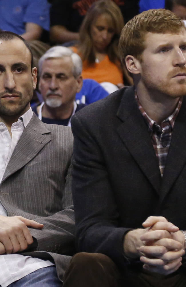 San Antonio Spurs' Manu Ginobili, left, and Matt Bonner, right, sit on the bench during an NBA basketball game against the Oklahoma City Thunder in Oklahoma City, Thursday, April 3, 2014. Oklahoma City won 106-94
