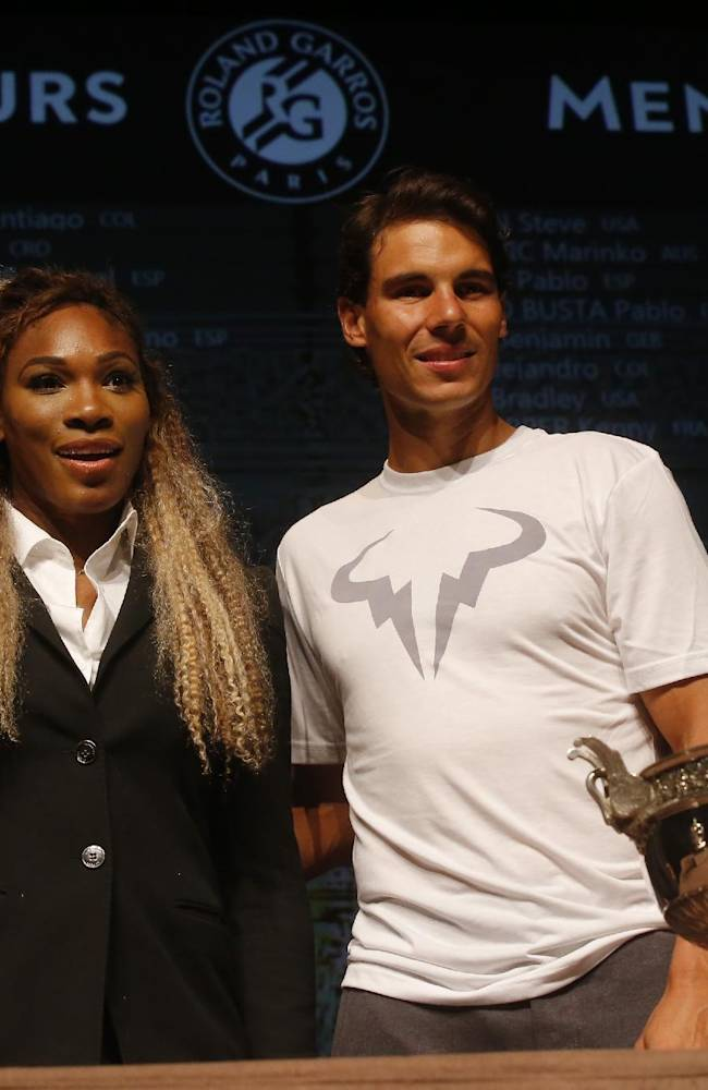 Defending champions Serena Williams, of the U.S, left, and Spain's Rafael Nadal pose during the draw for the French Open Tennis tournament, at the Roland Garros stadium in Paris, Friday, May 23, 2014. The French Open tennis tournament starts Sunday. At left is the women's trophy, at right, the men's trophy