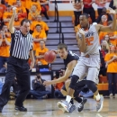 Oklahoma State guard Market Brown, right, tries to move out of the way of Gonzaga Guard Kevin Pangos, center, while the referee calls a foul during the first half of an NCAA college basketball game in Stillwater, Okla., Monday, Dec. 31, 2012. (AP Photo/Brody Schmidt)