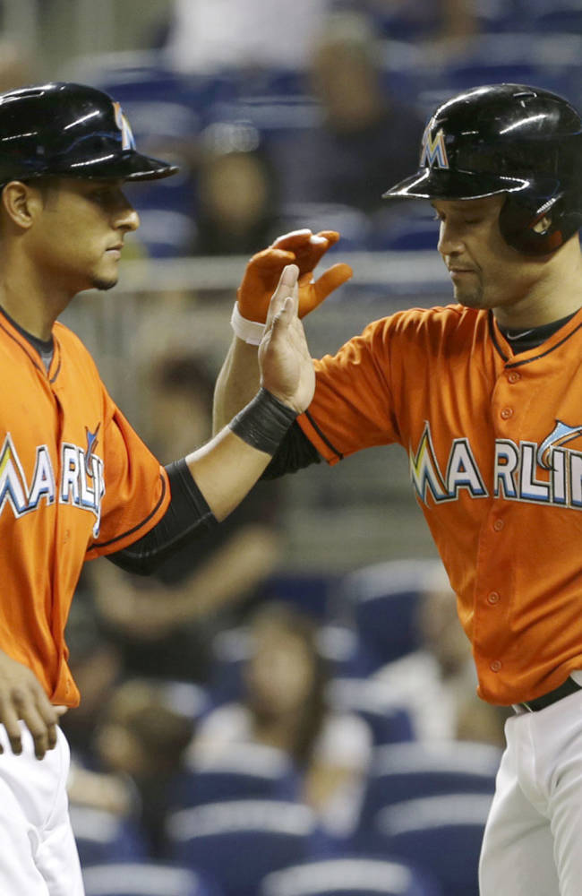 Miami Marlins' Donovan Solano, left, is congratulated by teammate Placido Polanco after Solano scored on a walk with the bases loaded by Philadelphia Phillies  relief pitcher Luis Garcia in the first inning of a baseball game,  Monday, Sept. 23, 2013, in Miami