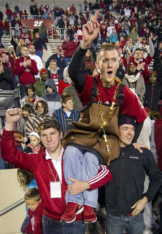 A fan, dressed to resemble the Old Oaken Bucket trophy, celebrates the team's victory on top of the shoulders of other fans at the end of an NCAA college football game Saturday, Nov. 30, 2013, in Bloomington, Ind. Indiana won 56-36 to win the Old Oaken Bucket trophy