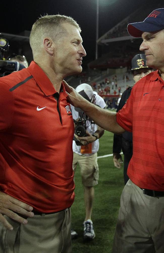 UNLV head coach Bobby Hauck, left, and Arizona head coach Rich Rodriguez talk after an NCAA college football game, Friday, Aug. 29, 2014, in Tucson, Ariz