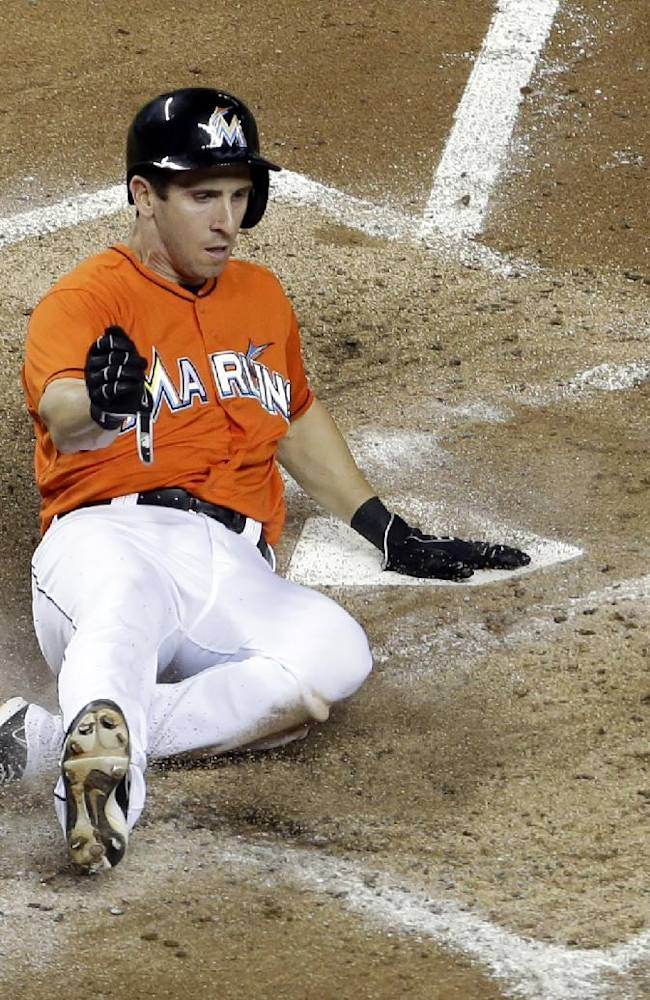 Miami Marlins' Ed Lucas scores on a single by Logan Morrison in the fourth inning during a baseball game against the Atlanta Braves, Wednesday, Sept. 11, 2013, in Miami
