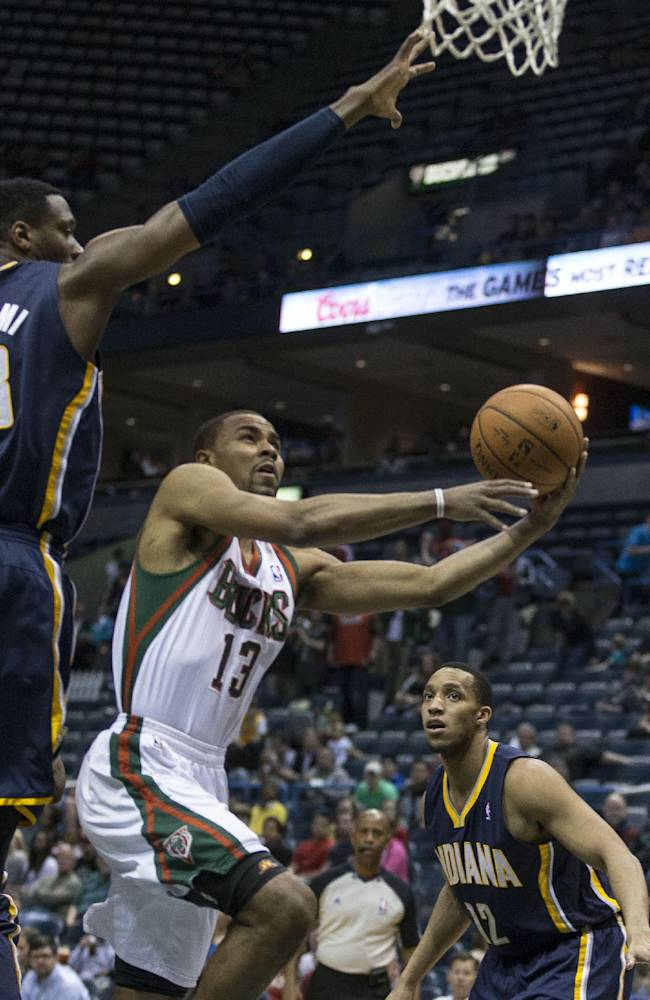 Milwaukee Bucks' Ramon Sessions (13) drives under Indiana Pacers' Ian Mahinmi during the first half of an NBA basketball game on Wednesday, April 9, 2014, in Milwaukee