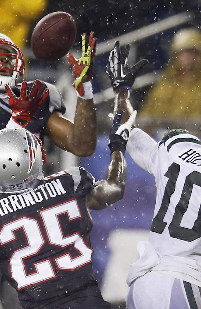 New England Patriots cornerback Aqib Talib, left, intercepts a pass intended for New York Jets wide receiver Santonio Holmes (10) in front of Patriots cornerback Kyle Arrington (25) during the fourth quarter of an NFL football game Thursday, Sept. 12, 2013, in Foxborough, Mass