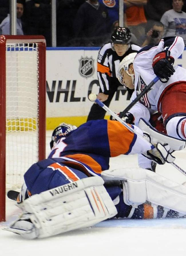 Columbus Blue Jackets' Cam Atkinson (13) shoots the puck past New York Islanders goalie Evgeni Nabokov (20) during an NHL hockey game on Saturday, Oct. 5, 2013, in Uniondale, N.Y