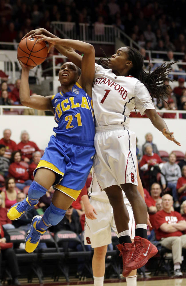 Stanford guard Lili Thompson, right, blocks a shot attempt by UCLA guard Nirra Fields (21) during the second half of an NCAA college basketball game on Friday, Jan. 24, 2014, in Stanford, Calif