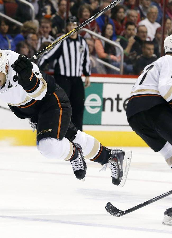 Anaheim Ducks' Ryan Getzlaf, left, gets tripped by Phoenix Coyotes' Rostislav Klesla (16), of Czech Republic, as Ducks' Dustin Penner (17) skates past during the second period of an NHL hockey game Saturday, Nov. 23, 2013, in Glendale, Ariz