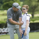 Stephen Gallacher of Great Britian, kids around with his 12-year-old son, Jack, on the putting green during practice at the WGC Bridgestone Invitational golf tournament, at Firestone Country Club in Akron, Ohio, Tuesday, July 30, 2013. The tournament starts Thursday. (AP Photo/Phil Long)