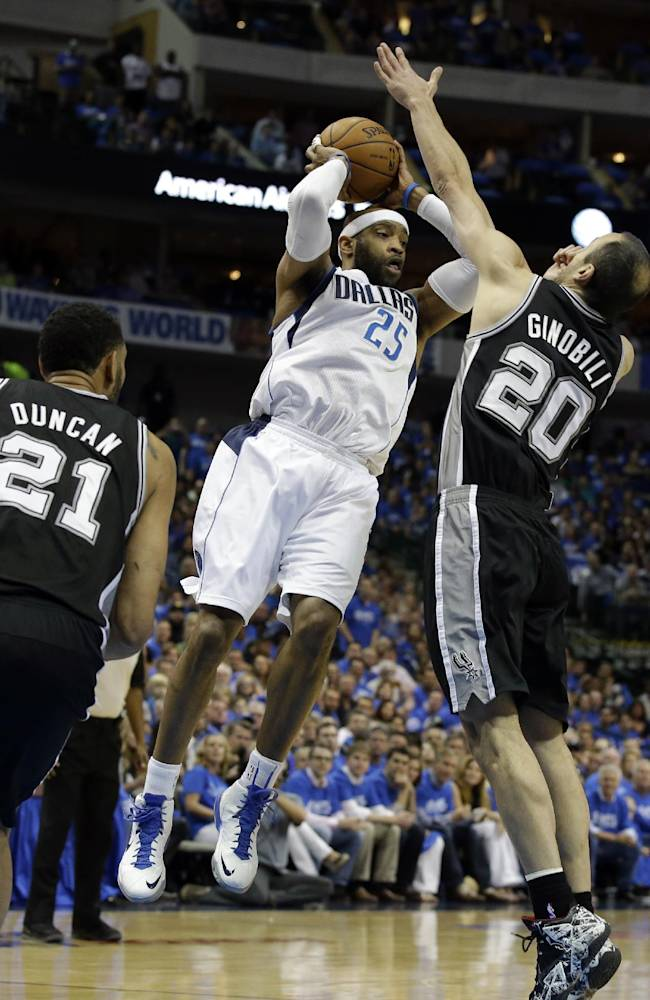 San Antonio Spurs' Tim Duncan (21) watches as Dallas Mavericks' Vince Carter (25) passes the ball under pressure from Spurs' Manu Ginobili (20), of Argentina, in the first half of Game 6 of an NBA basketball first-round playoff series on Friday, May 2, 2014, in Dallas. (AP Photo/Tony Gutierrez)