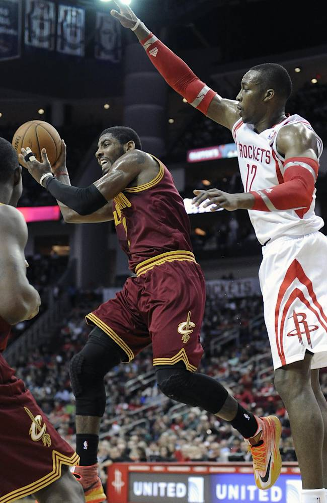 Cleveland Cavaliers' Kyrie Irving, left, passes the ball away from Houston Rockets' Dwight Howard (12) in the first half of an NBA basketball game Saturday, Feb. 1, 2014, in Houston