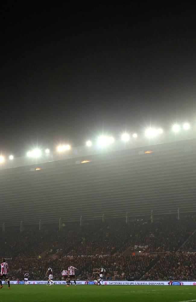 A general view of the fog setting in over the English Premier League soccer match between Sunderland, playing in red stripes, and West Ham United at the Stadium of Light, Sunderland, England, Monday, March 31, 2014