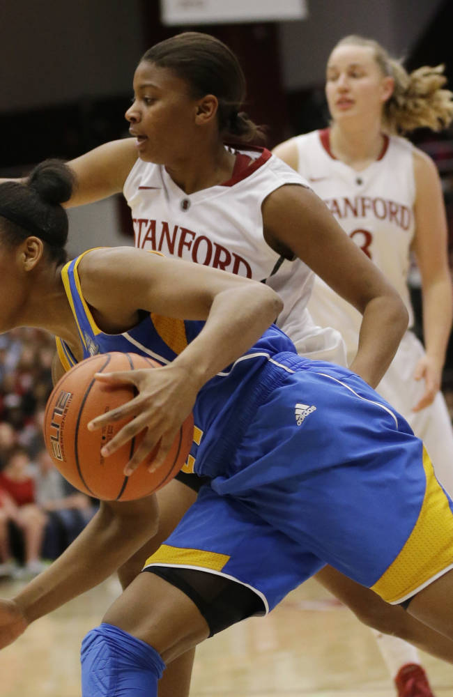 UCLA guard Nirra Fields, bottom, dribbles past Stanford guard Amber Orrange during the second half of an NCAA college basketball game on Friday, Jan. 24, 2014, in Stanford, Calif