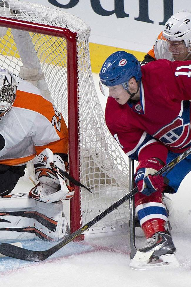 Montreal Canadiens' Brendan Gallagher, center, moves in on Philadelphia Flyers' goaltender Ray Emery, left, as Flyers' Kimmo Timonen defends during the second period of an NHL hockey game in Montreal, Saturday, Oct. 5, 2013