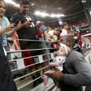 Arizona Cardinals' Patrick Peterson, right, poses for a picture with two-month-old Ariana Ortiz, as her mother Maria Ortiz, left, of Phoenix, snaps the photo with her phone after Cardinals NFL football training camp practice on Wednesday, July 30, 2014, i
