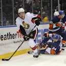Ottawa Senators' Mark Stone (61) drives the puck past a fallen New York Islanders' Kevin Czuczman (24) as Islanders' Scott Mayfield (42) starts to give chase during the first period of an NHL hockey game Tuesday, April 8, 2014, in Uniondale, N.Y. The Sena