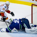 Vancouver Canucks' goalie Eddie Lack, right, of Sweden, covers up the puck as Calgary Flames' Mikael Backlund, also of Sweden, tries to poke it free during first-period NHL hockey game action in Vancouver, British Columbia, Saturday, March 8, 2014 The Ass