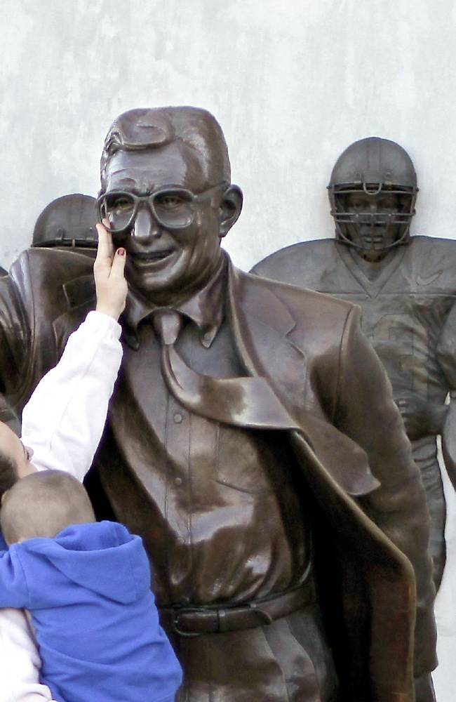 In this Oct. 8, 2010 file photo, Ashley Buchan holds her 4-year-old nephew Caleb Anthony, as she reaches to touch the face of the statue of former Penn State football coach Joe Paterno outside Beaver Stadium in State College, Pa. In 2012, the school removed this Paterno statue after a university-commissioned report accused the late coach and three other administrators of concealing sex abuse claims against retired assistant coach Jerry Sandusky. Fans of the late coach are commissioning a new statue to be placed across from the school at a local restaurant