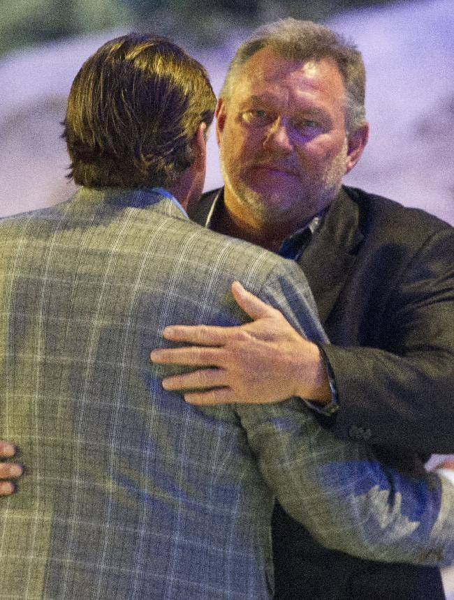 Former Houston Oilers Carl Mauck, front, and Dan Pastorini hug during a memorial service for Bum Phillips on Tuesday, Oct. 29, 2013, in Houston. Phillips, the former Oilers and New Orleans Saints coach, died Oct. 18 at age 90