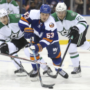 New York Islanders center Casey Cizikas (53) reaches for the puck as Dallas Stars center Shawn Horcoff (10) and center Colton Sceviour (22) give chase during the second period of an NHL hockey game, Saturday, Oct. 25, 2014, in Uniondale, N.Y The Associate