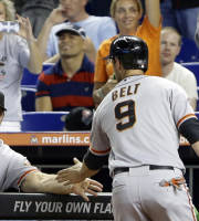San Francisco Giants manager Bruce Bochy, left, congratulates Brandon Belt (9) after Belt and Hunter Pence scored on a double by Pablo Sandoval during the first inning of a baseball game against the Miami Marlins, Friday, Aug. 16, 2013, in Miami. (AP Photo/Wilfredo Lee)