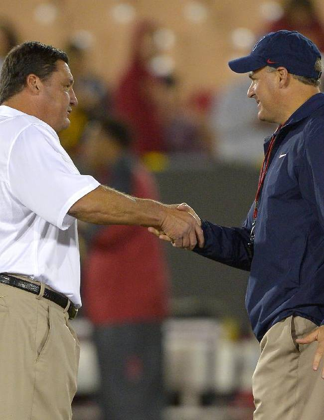 Southern California interim coach Ed Orgeron, left, greets Arizona coach Rich Rodriguez prior to an NCAA college football game, Thursday, Oct. 10, 2013, in Los Angeles