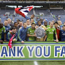 Seattle Sounders players celebrate with the Supporters' Shield trophy after they defeated the Los Angeles Galaxy 2-0 in an MLS soccer match, Saturday, Oct. 25, 2014, in Seattle. The Supporters' Shield is awarded to the MLS team with the best regular-seaso